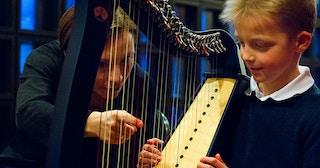 En musiker demonstrerer harpe under familiedagen